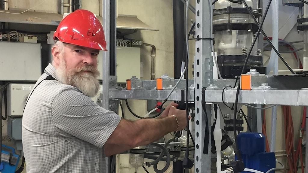 Christian Ekberg står i en labbverkstad och tittar in i kameran.