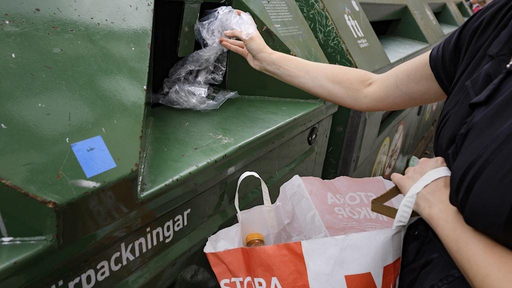 Person med svart t-shirt stoppar in plastskräp i grön återvinningscontainer. I andra handen håller hen en pappkasse.