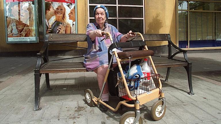 Äldre dam på bänk.