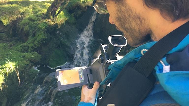 En man mäter vattentemperatur med hjälp av en kamera.