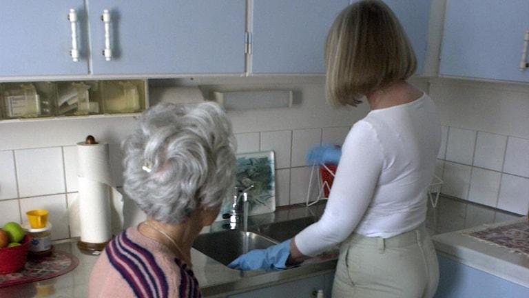 En äldre kvinna får hjälp i köket av en kvinnlig person.