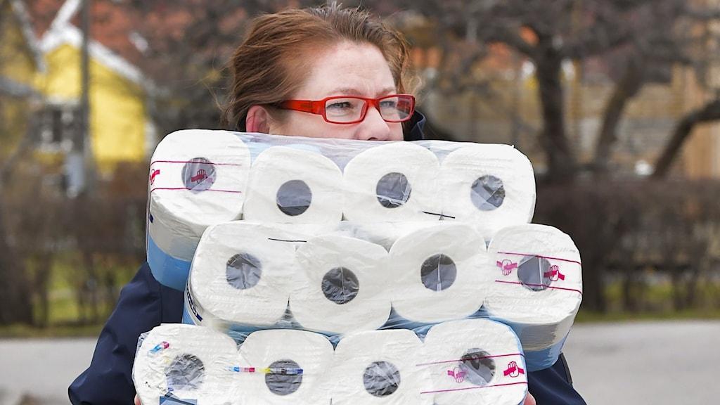 En kvinna som bär på flera balar toalettpapper.
