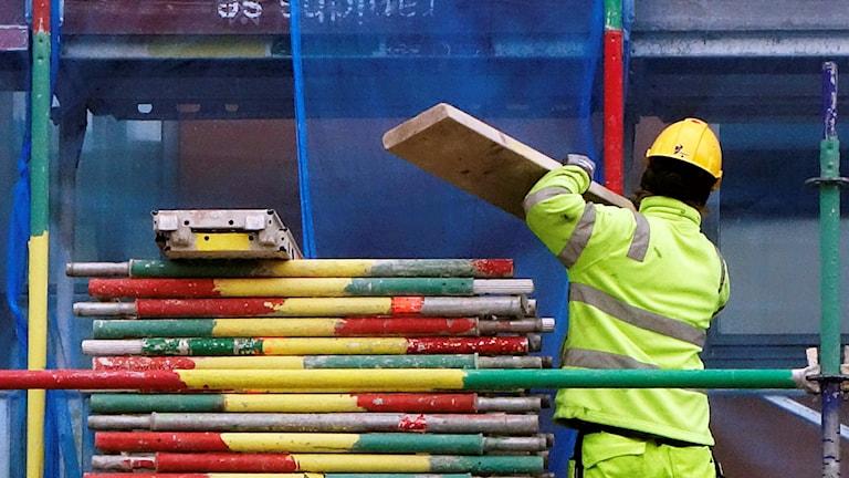 En byggarbetare på en färgglad byggställning.