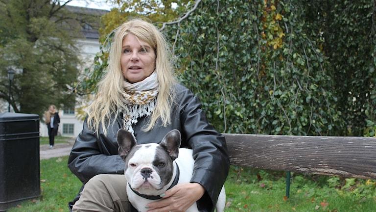 En kvinna med långt blont hår sitter på en parkbänk med en svar och vitt fransk bulldog.