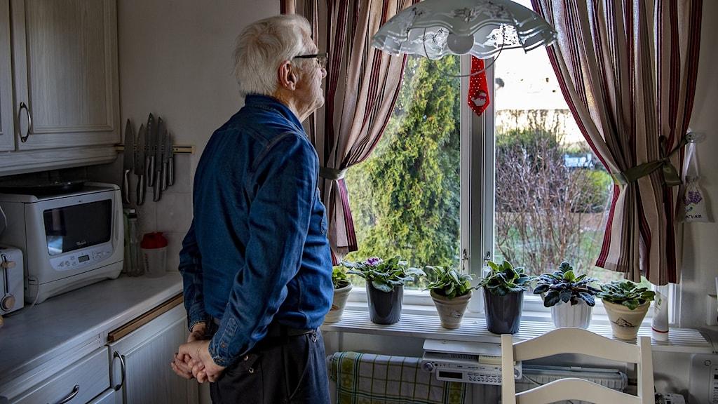 En man står och tittar ut genom fönstret