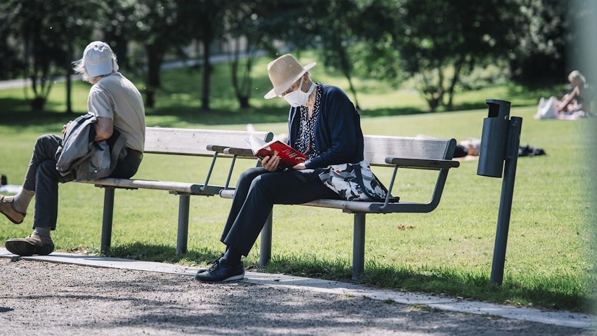 En kvinna sitter på en parkbänk med munskydd och läser en bok