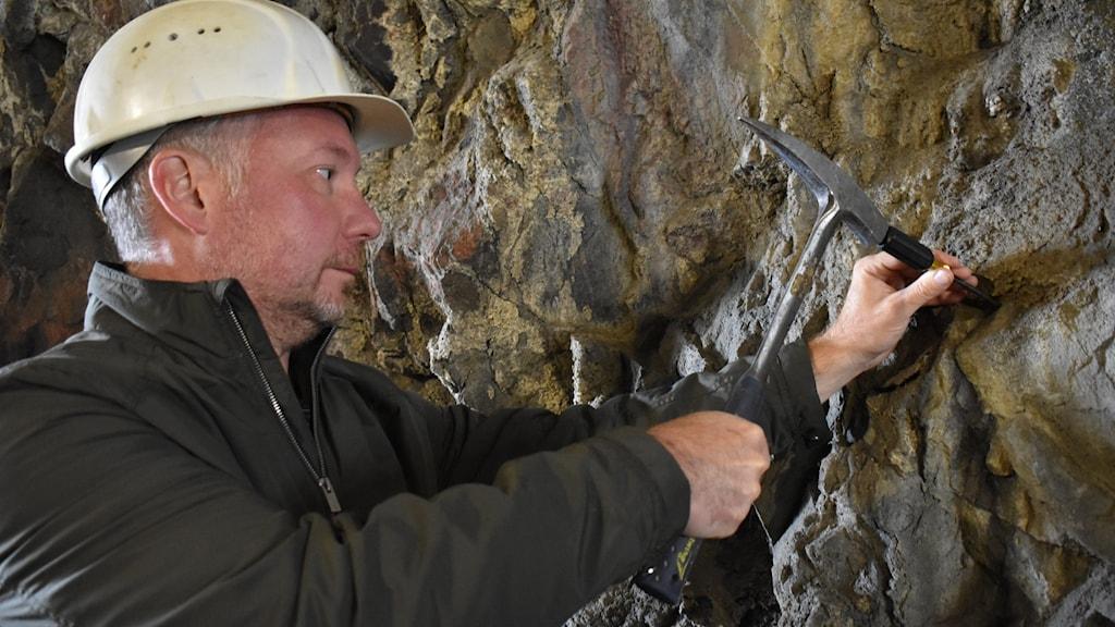 En man med skyddshjälm arbetar i en gruva
