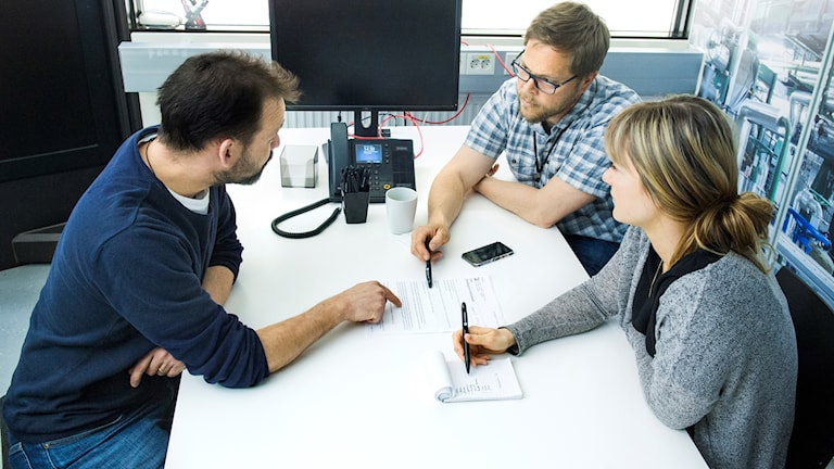 Tre personer sitter i ett möte på ett kontor