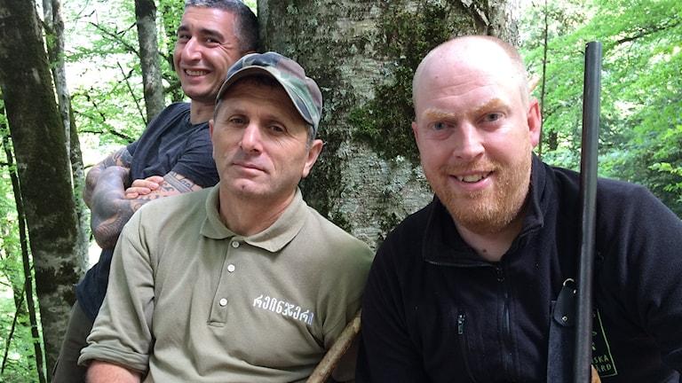 tre män framför tjock trädstam. En med gevär.