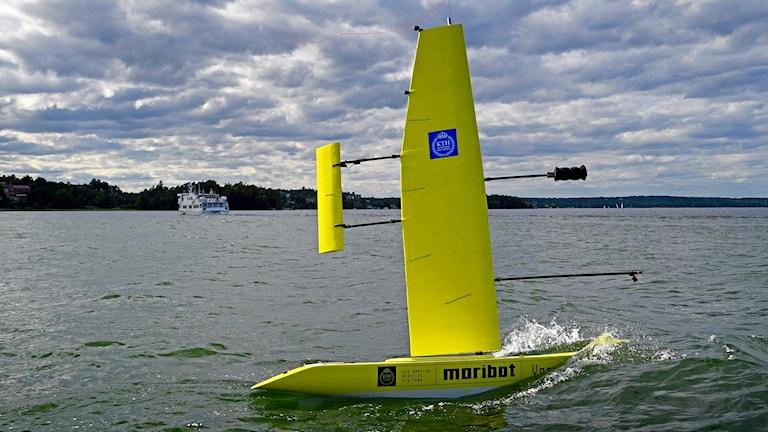 En självseglande gul segelbåt som är ute på sjön. I bakgrunden syns en större båt, och himlen ovanför är molnig.