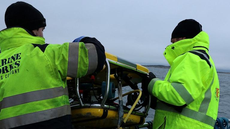 Två personer välter en gul robot över relingen på båt.