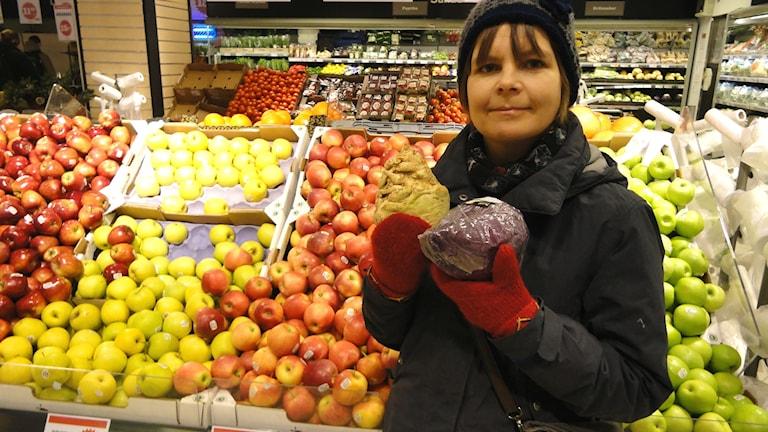 Elin Röös, som forskar om mat och miljö vid Sveriges lantbruksuniversitet, håller upp grönsaker där hon står framför fruktdisken i en livsmedelsbutik.