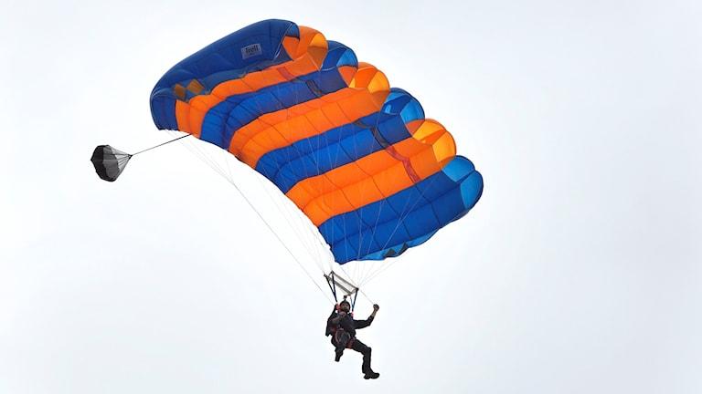 En fallskärmshoppare på väg ner mot marken.