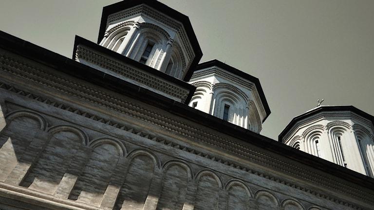 Fasaden och några torn på det rumänska klostret Radu Voda sett från marken.