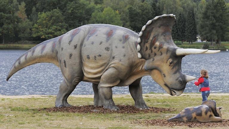 Barn framför en modell av dinosaurie.