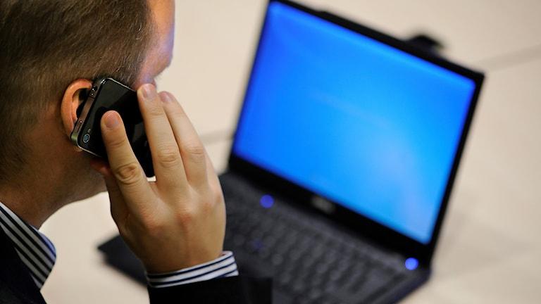 En man pratar i en smart telefon framför en bärbar dator.