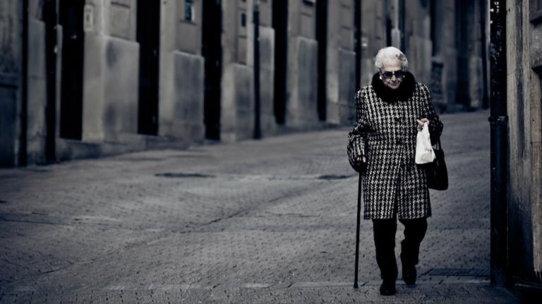 En dam i rutig kappa promenerar på en tom gata