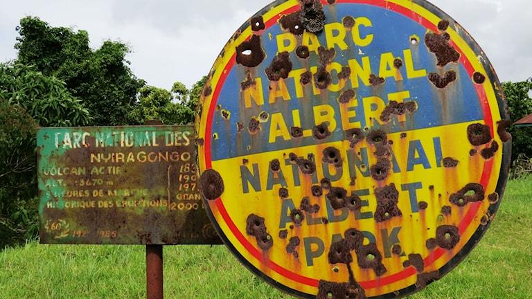 En gammal skylt vid Virunga nationalpark som är full med kulhål efter att ha blivit beskjuten.