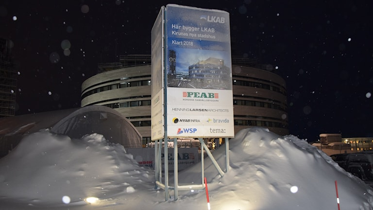 """Det snart klara stadshuset i Kiruna, en rund byggnad, i mycket snö. Framför den en skylt med texten: """"Här bygger LKAB Kirunas nya stadshus, klart 2018."""