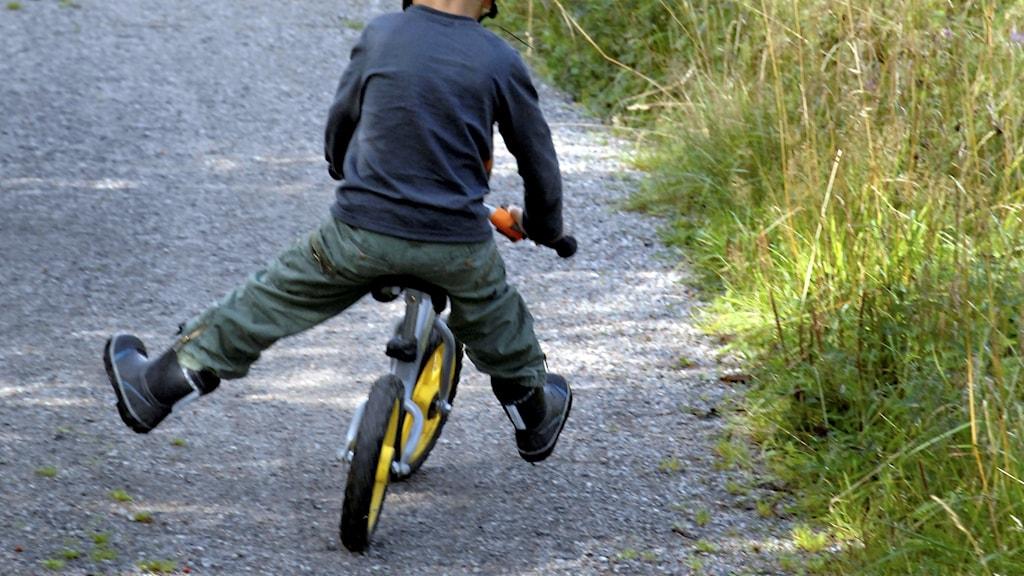 Ett barn på cykel utan pedaler