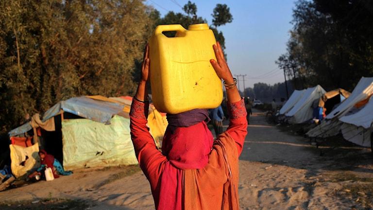 Kvinna  med vattendunk på huvudet
