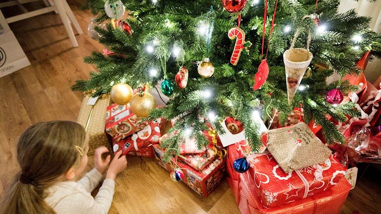 julgran med paket och ett barn