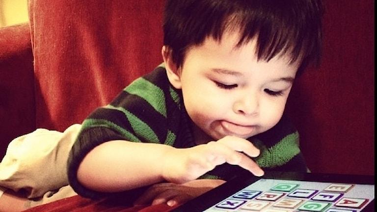 En liten pojke ligger och spelar spel på ipad