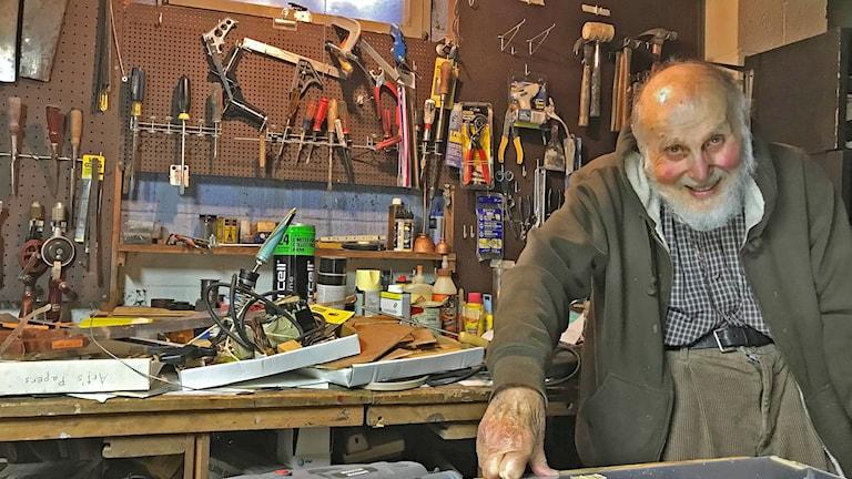 Arthur Ashkin i sin källare, omgiven av en massa verktyg på bordet bakomhonom och på väggen.