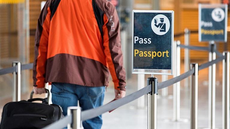 En man i orange jacka går mot passkontrollen