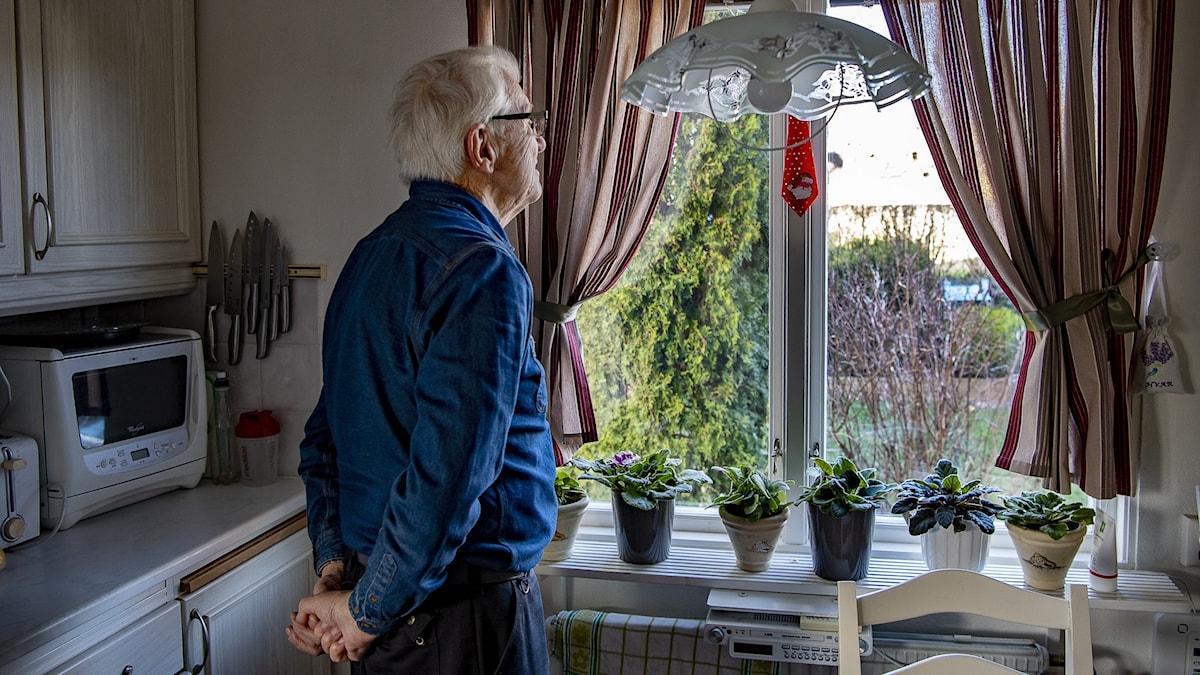 Ensam man tittar ut genom sitt köksfönster.