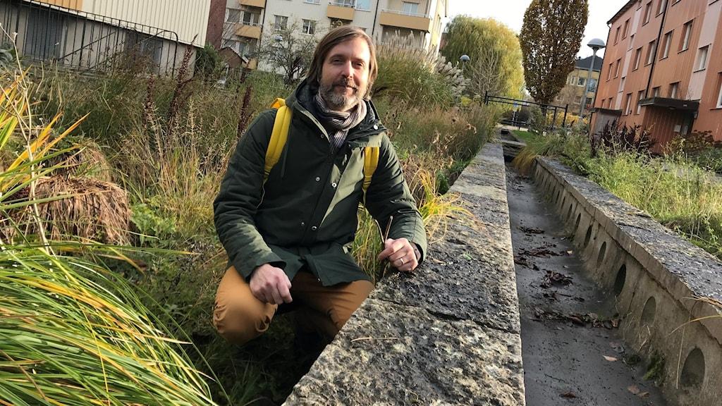 Man med grön jacka, bryna byxor och gul ryggsäck sitter på huk bland högt gräs och håller armen mot en låg stenmur.