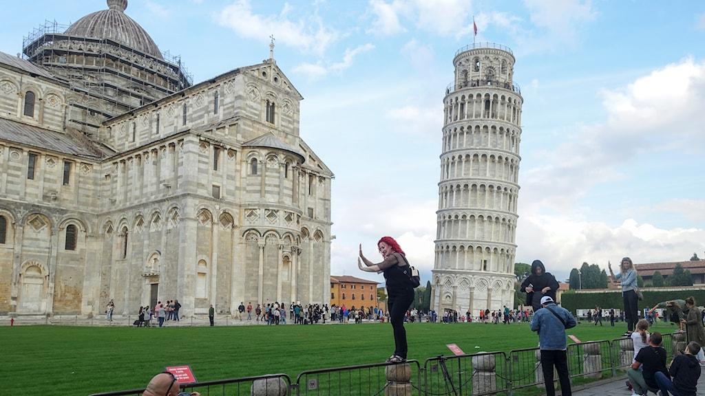 Lutande tornet i Pisa med turister i förgrunden.