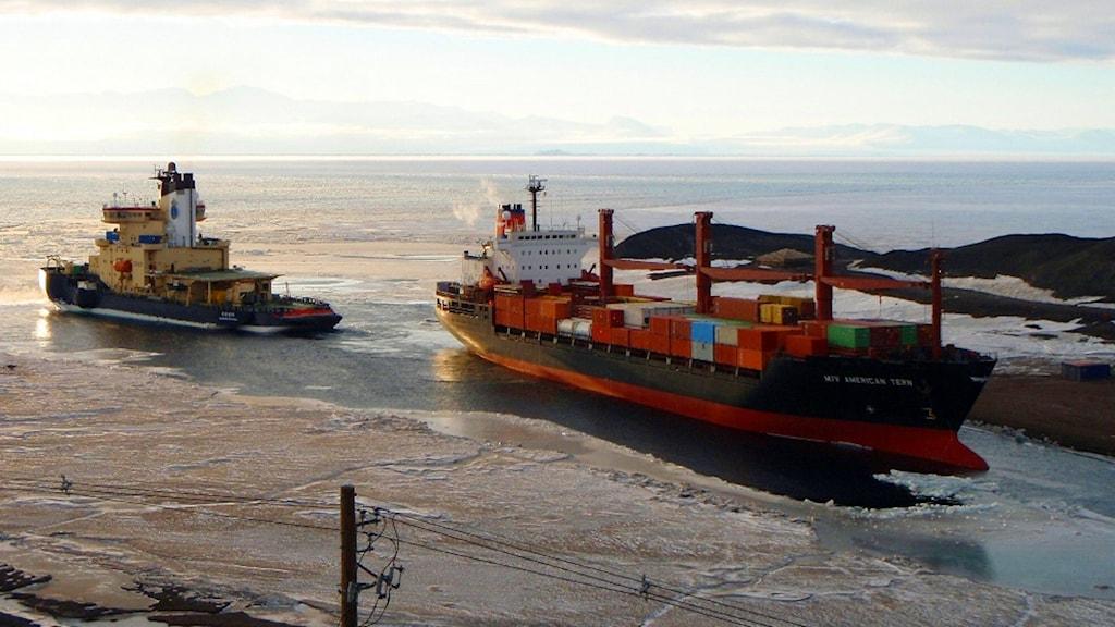 Isbrytaren Oden guidar ett större fartyg ut ur en hamn.