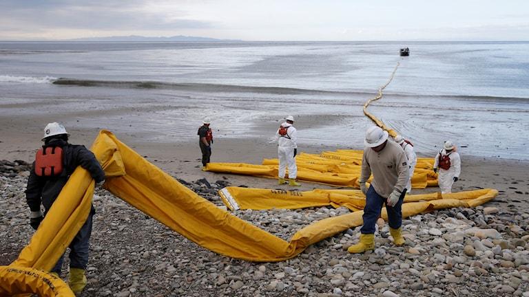 Arbetare förbereder anordning som ska stänga in olja