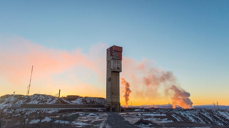 bild på Kiruna gruva i gryningen. Rökpelare stiger mot en guldskimrande vinterhimmel.