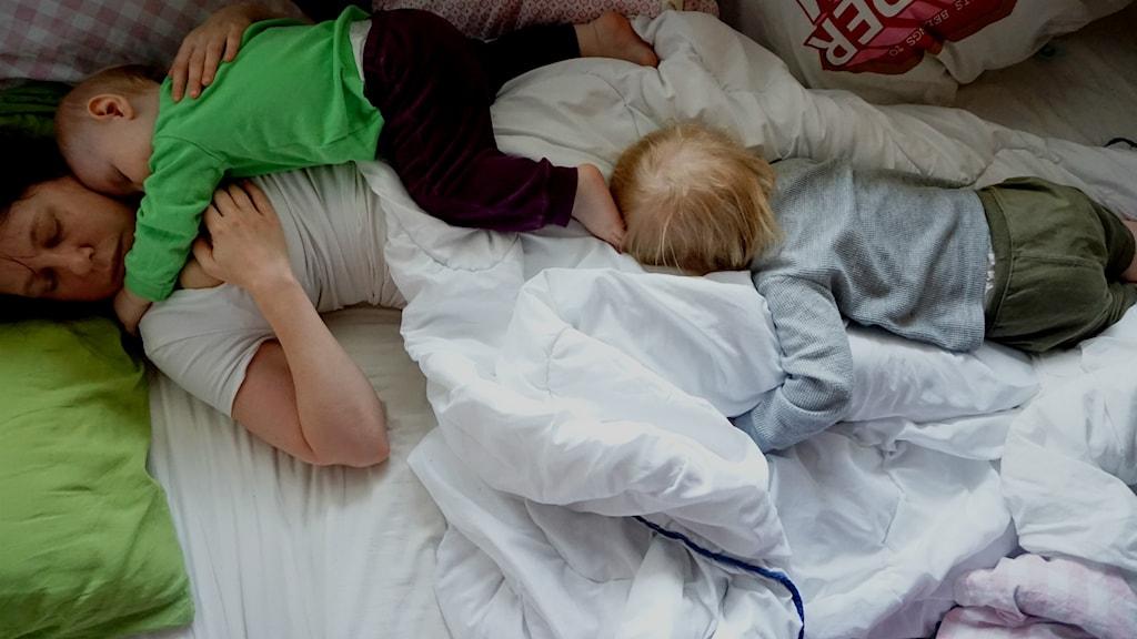 En kvinna och två barn sover i en säng.