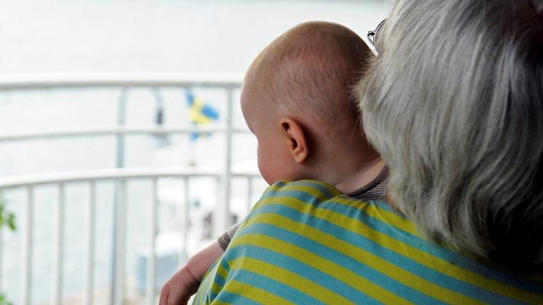 Gammal människa som håller i ett barn.