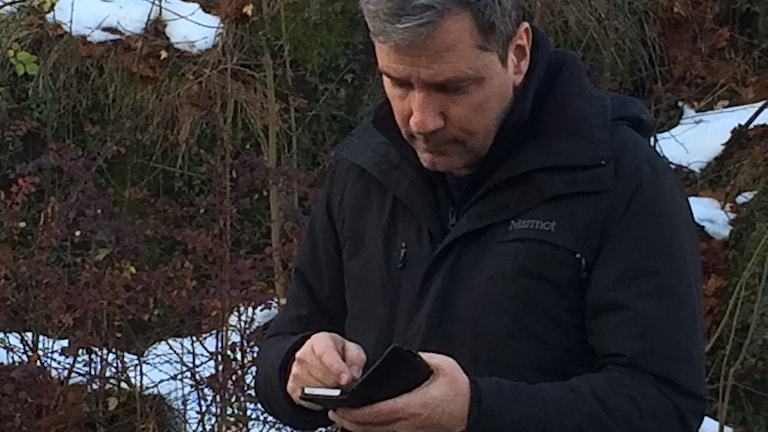 Pokémon Go-spelare. 54-årig man, grått kort hår, svart jacka, snö och buskar i bakgunden