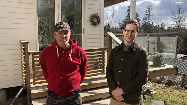 Två män framför ett hus med altan.