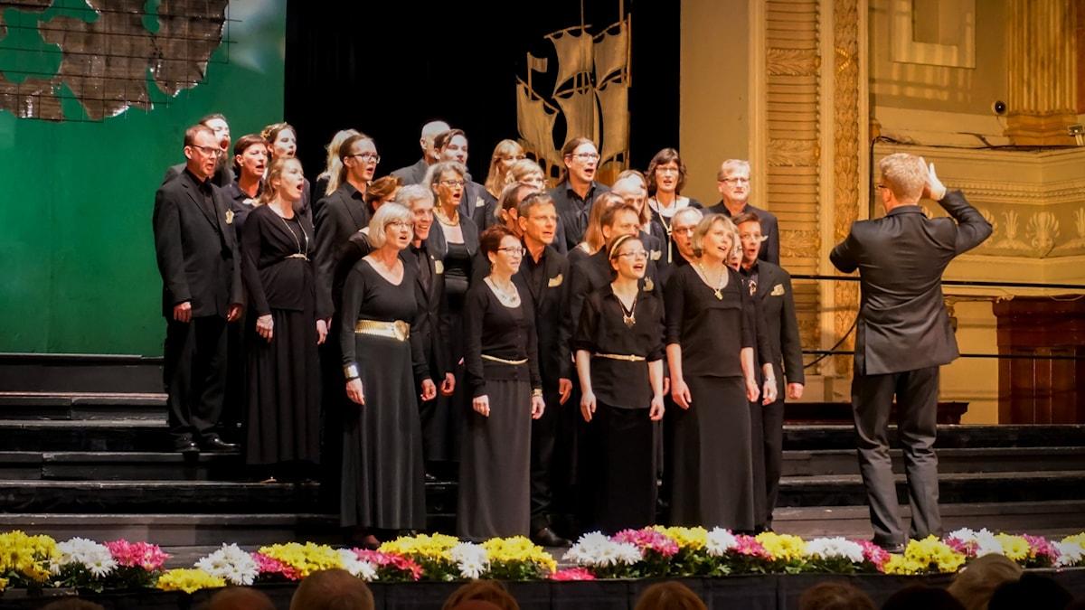 En grupp människor i svarta kläder står framför en dirigent som har ryggen vänd mot kameran.
