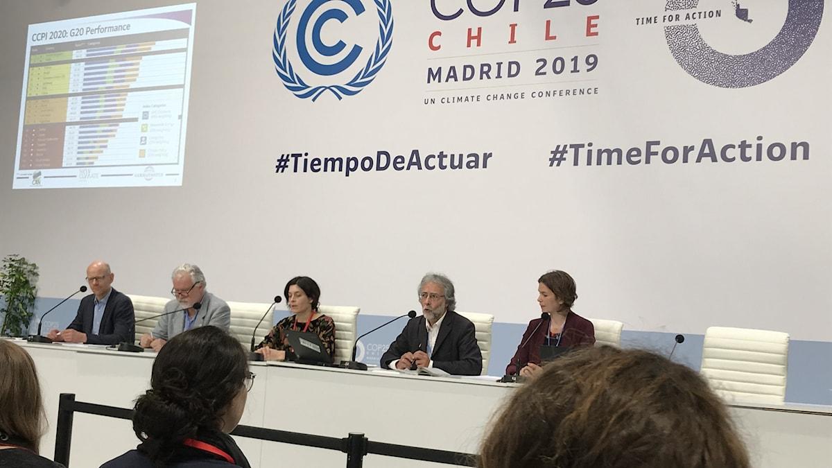 Fem personer sitter vid ett podium framför vit  vägg med text. Publik betraktar dem.