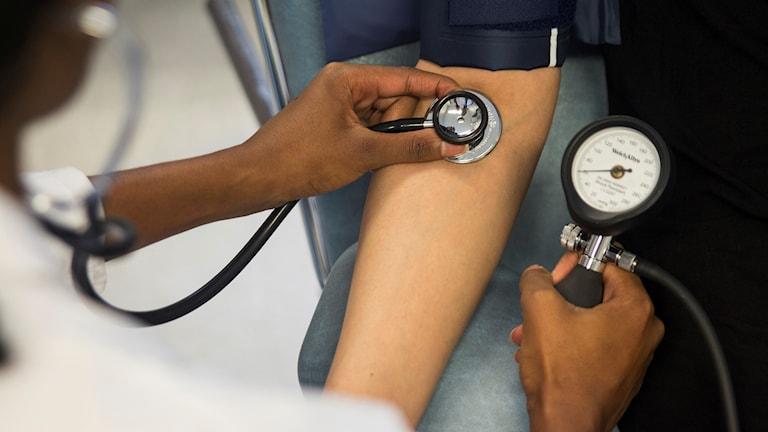 En person får blodtrycket kontrollerat.