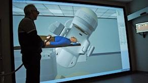 En man står framför en stor strålningssimulator.
