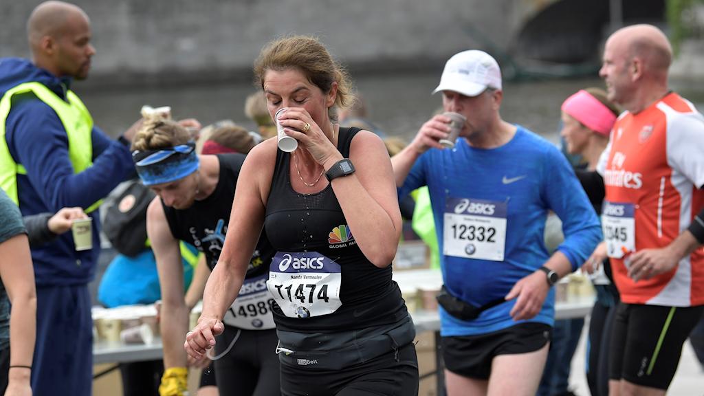 Kvinnor och män dricker vätska under Stockholm marathon 2019