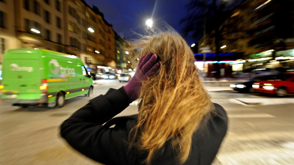 en kvinna står i en gatukorsning och håller för öronen