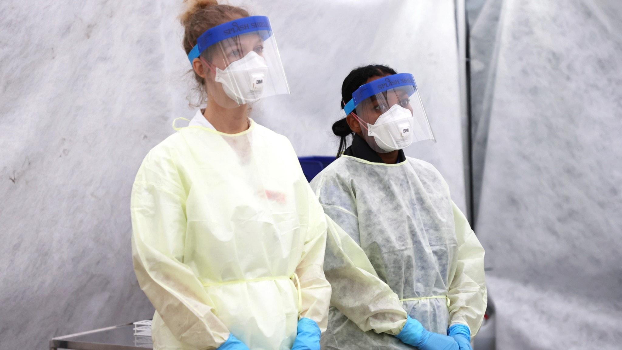 Två personer i skyddsdräkter och munskydd