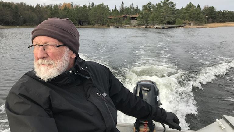 Äldre man med vitt skägg och glasögon och iförd mössa och handskar kör båt med utombordare bort från en ö.