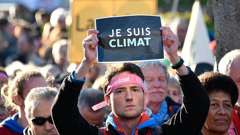 Person som håller upp en skyllt med orden Je suis climat, jag är klimatet.