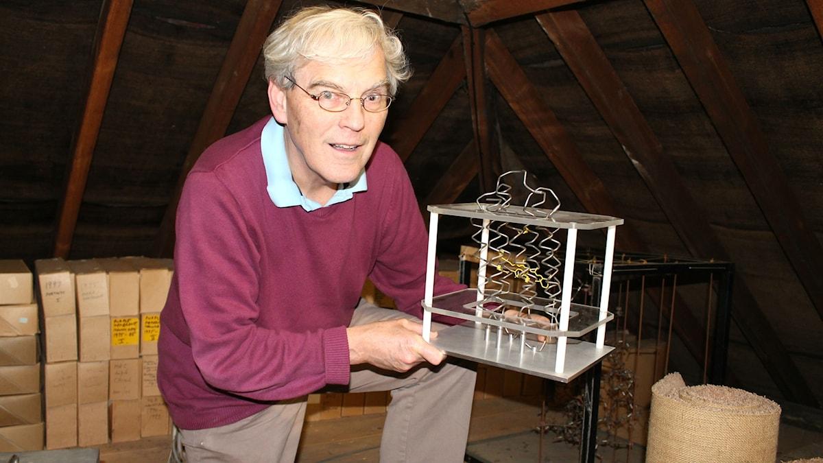 Nobelpristagaren Richard Henderson håller i en modell av ett membranprotein.
