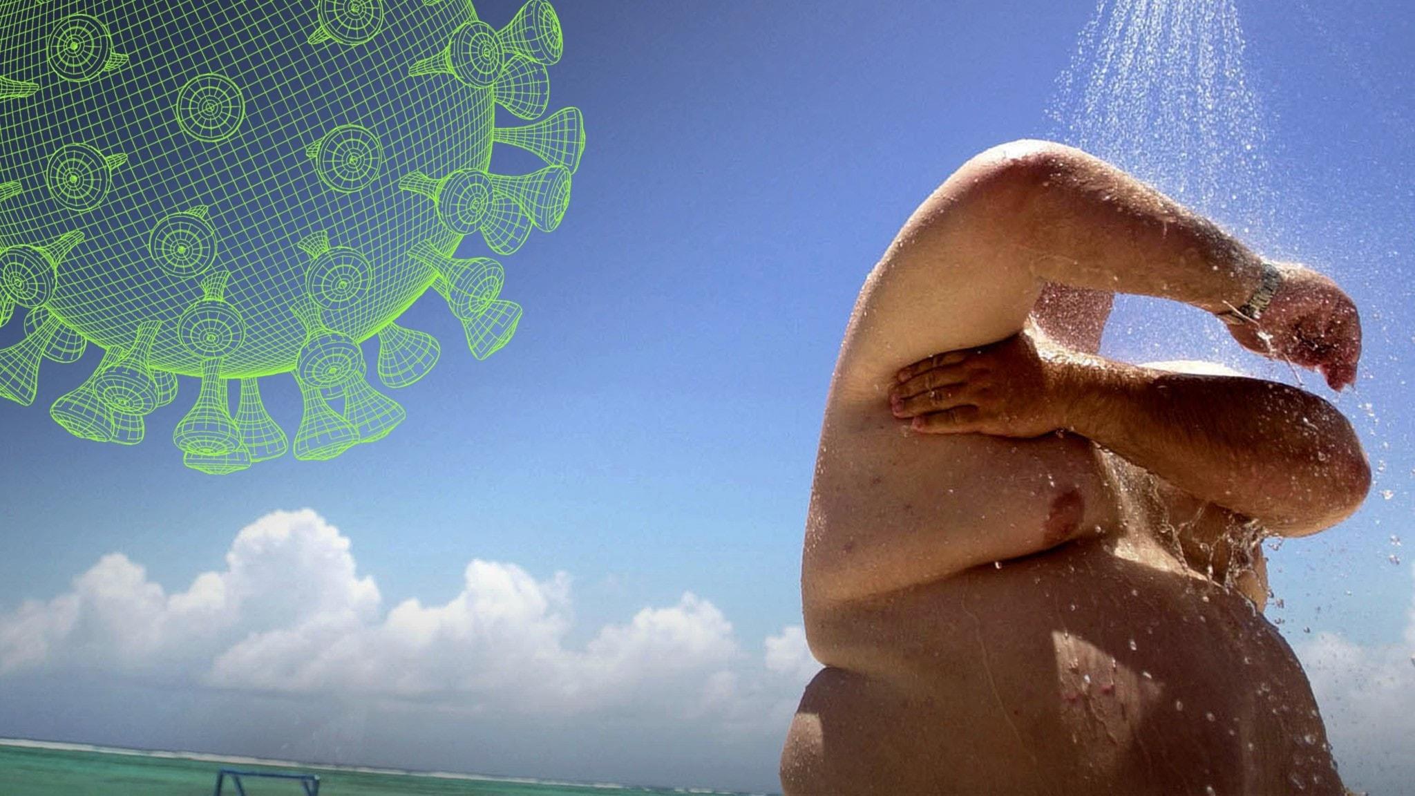 En man med övervikt står på en solig strand och duschar